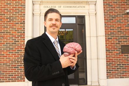 Dr. Griffin holds a model of a brain